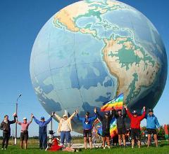 Vor einer riesigen Weltkugel halten sich Bike for Peace Teilnehmer an den Händen.